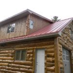 Hand_Scribed_Log_Siding_With_Rough_Pine_Planks_at_Shed_Roofs